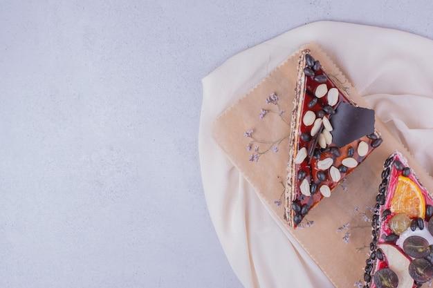 초콜릿과 과일 나무 보드에 삼각형 케이크 조각 무료 사진