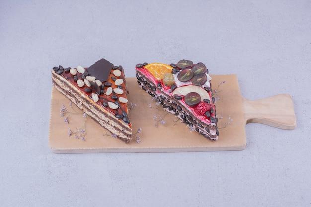 木の板にチョコレートとフルーツの三角形のケーキスライス