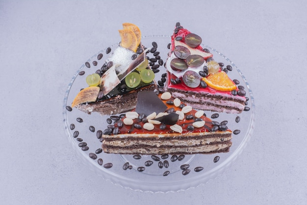 Triangle cake slices with chocolate and fruits in a glass platter