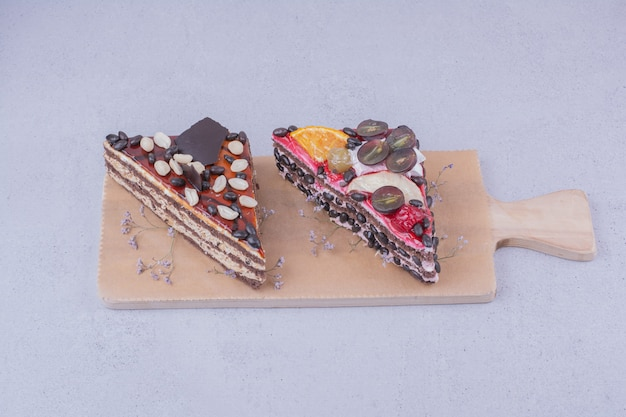Triangle cake slices with chocolate and fruits on a wooden board