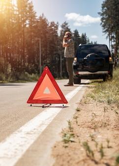 道路上の三角形の警告サインと緊急修理サービスを待っている携帯電話で話している人