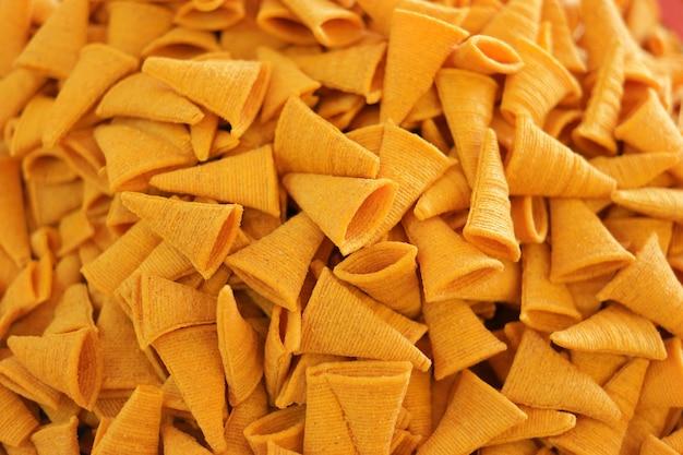 삼각형 바삭 바삭한 옥수수 치즈 맛 스낵 배경. 바삭한 매운 옥수수 스낵의 배경입니다.