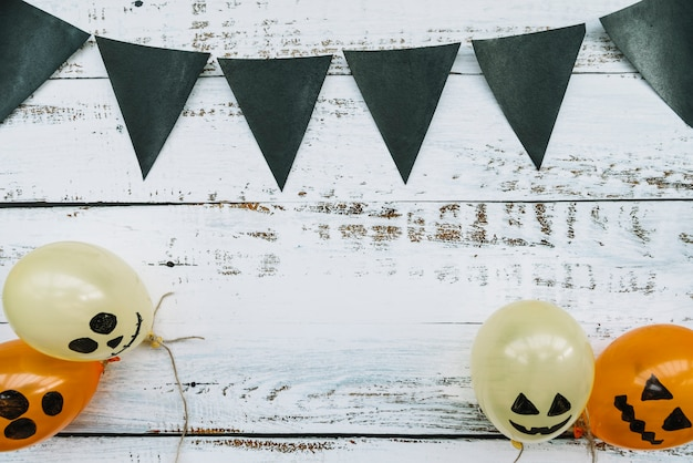 Triangle dark flags hanging above and balloons with creepy faces below on wooden background