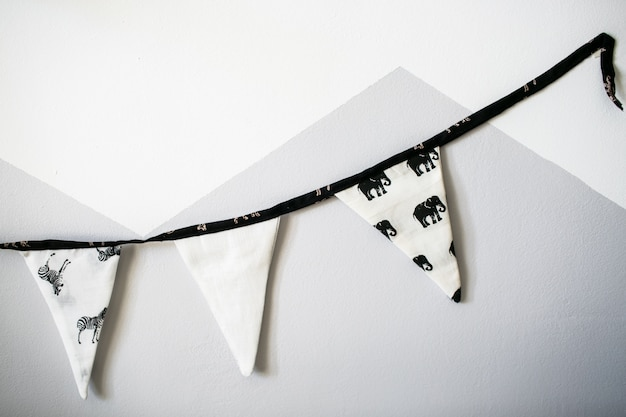 Triangle flag chain on the white and grey wall