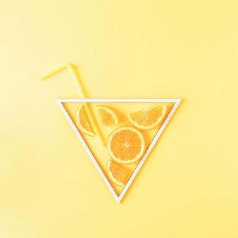 Треугольная рамка с кусочками апельсина на желтом фоне сюрреалистическая концепция коктейля