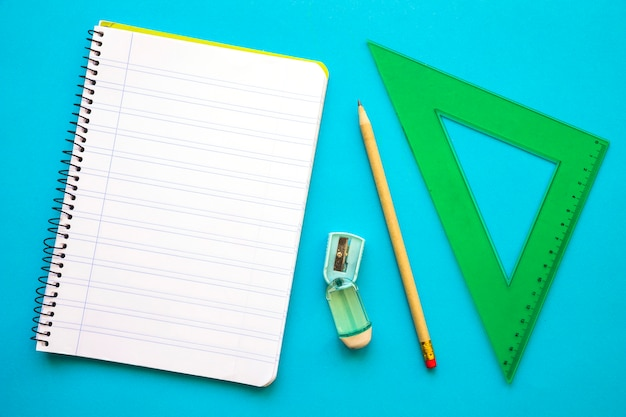 Triangle and notebook near pencil and sharpener