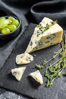 Треугольник голубого сыра с виноградом на разделочной доске. черный фон. вид сверху.