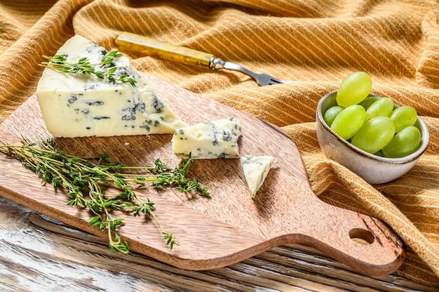 Треугольник голубого сыра с виноградом. белый деревянный фон. вид сверху. скопируйте пространство.