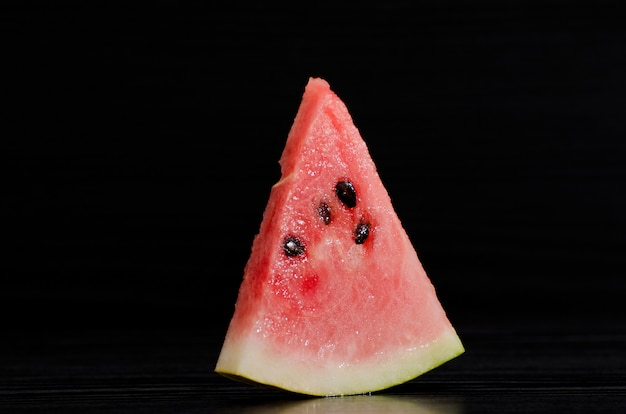 Triangle ripe watermelon on a black background