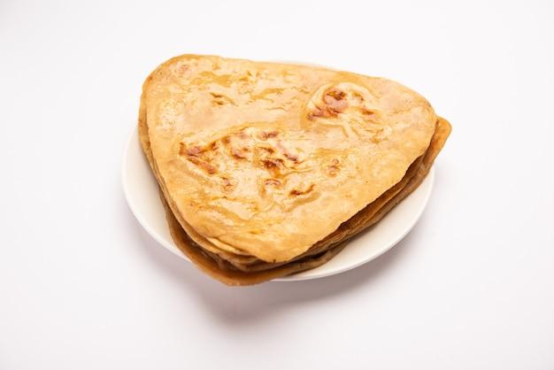 三角形のプレーンパラタまたはパランタは、全粒小麦粉で作られたおいしいインドのフラットブレッドです。プレートで提供、選択的な焦点