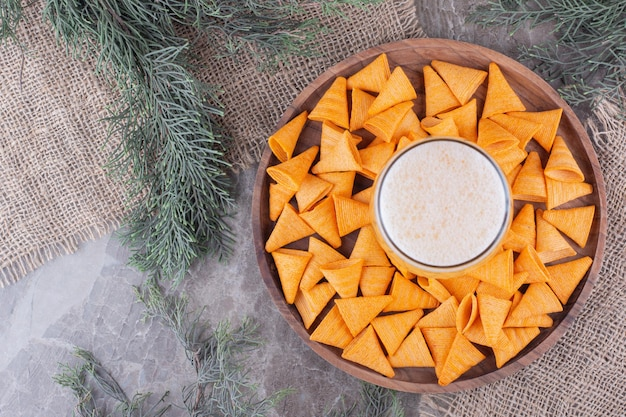 Triangle shaped chips and glass of beer on wooden plate. high quality photo