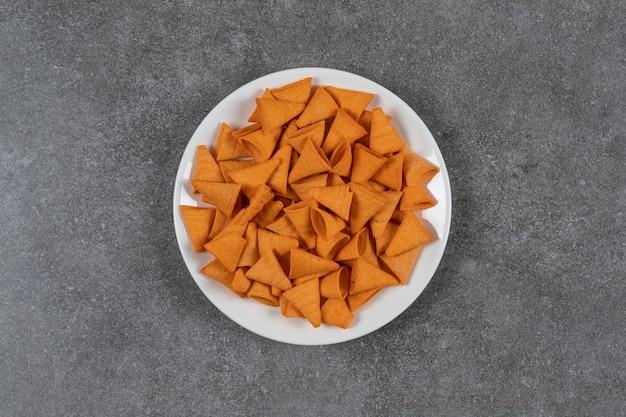 Chip a forma di triangolo sul piatto bianco.