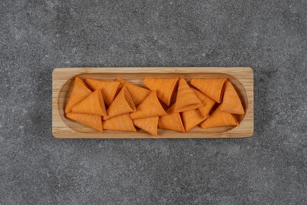 Chip a forma di triangolo sul piatto di legno.