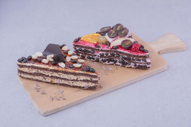 Ломтики шоколадного торта треугольной формы с орехами и фруктами на деревянном блюде