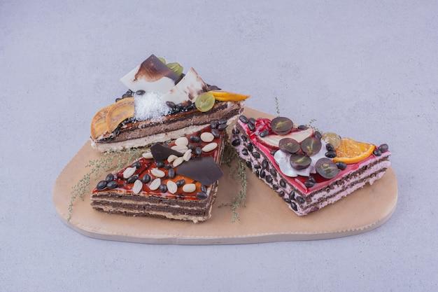 Fette di torta al cioccolato a forma di triangolo con noci e frutta su un piatto di legno