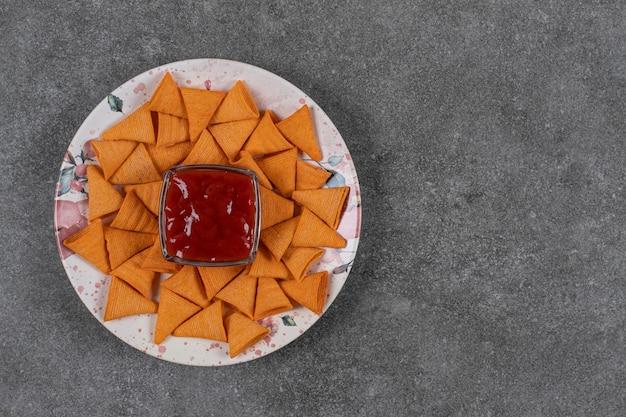 케첩과 접시에 삼각형 모양의 크래커.