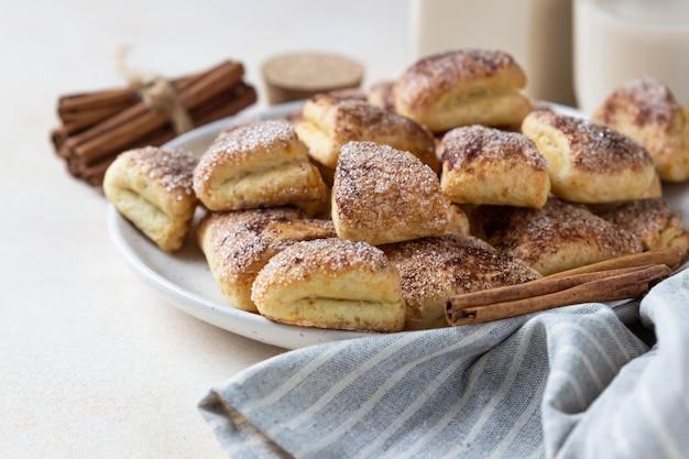 カッテージチーズのクッキーを砂糖とシナモンで三角形にします。ガチョウまたはカラスの足のクッキー。