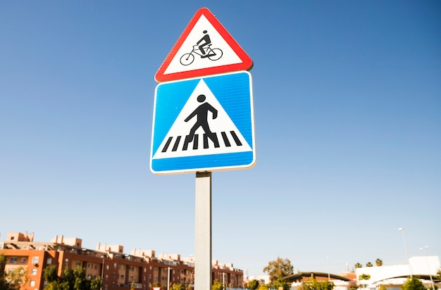 Triangular bicycle warning sign over the square pedestrian crossing road sign in the city