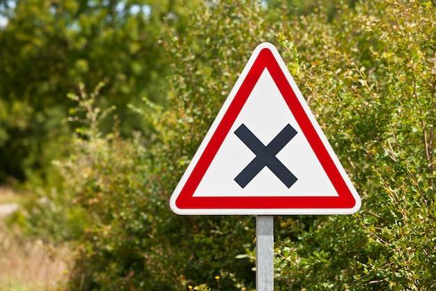 田舎道のジャンクションの三角形の交差点の道路標識