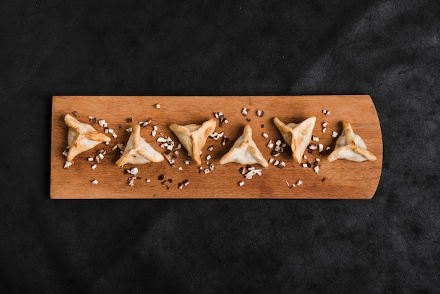 Triangular dumplings on wooden tray over the black background