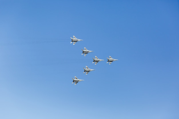 A triangular formation of a group of six russian military fighter jet planes flying high in blue sky
