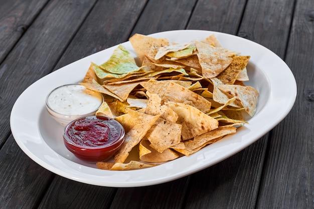 Треугольные чипсы начос с томатным кетчупом и сырным соусом на тарелке