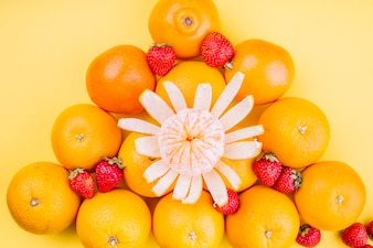 Triangular oranges with strawberries on yellow backdrop