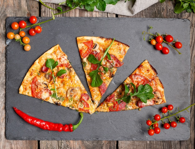 Triangular piece of baked pizza with mushrooms, smoked sausages, tomatoes