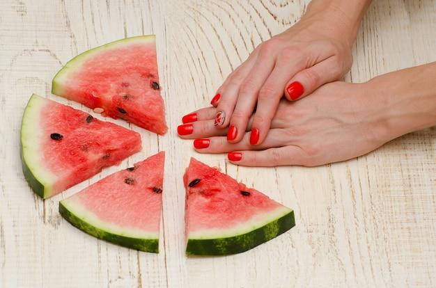 スイカの三角形の部分と明るい木製のマニキュアで女性の手