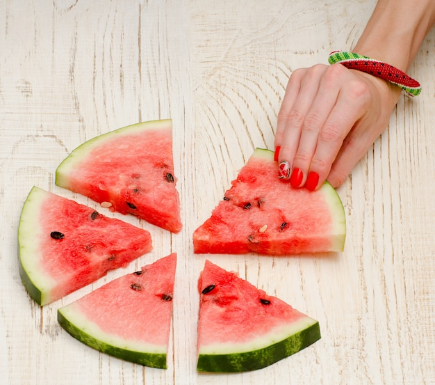 Triangular pieces of watermelon and woman's hands with a manicure on a light wooden
