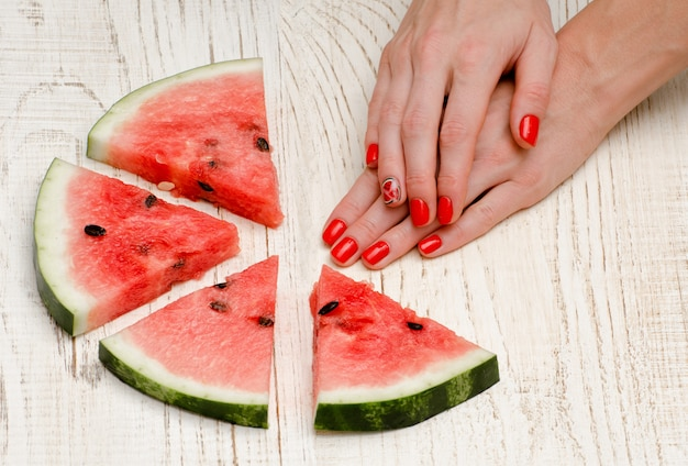 Triangular pieces of watermelon and woman's hands with a manicure