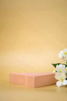 Triangular podium for the demonstration of cosmetics, products on a beige background and jasmine