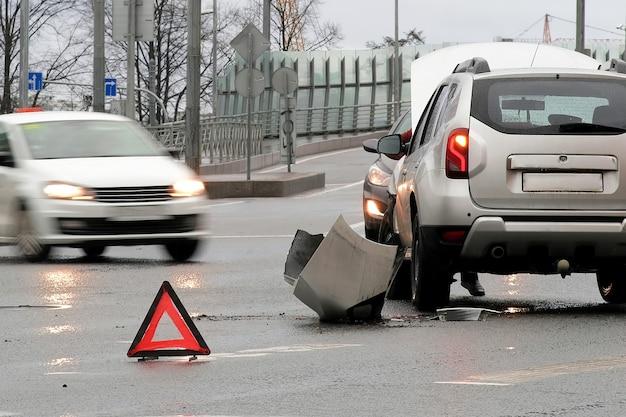 道路上の事故の三角形の赤い再帰反射サイン。 2台の車の衝突。壊れたバンパーとフード。路上での自動車事故。