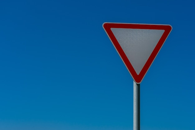Triangular road sign (give way) close-up on a blue sky background.