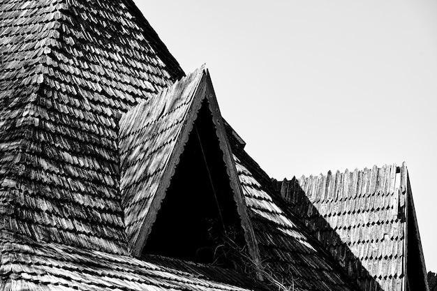 Треугольная крыша с деревянной черепицей заброшенного дома