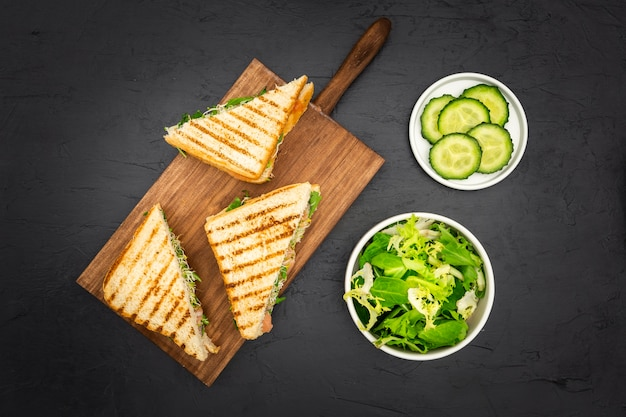 Triangular sandwiches on chopping board with salad and cucumber slices