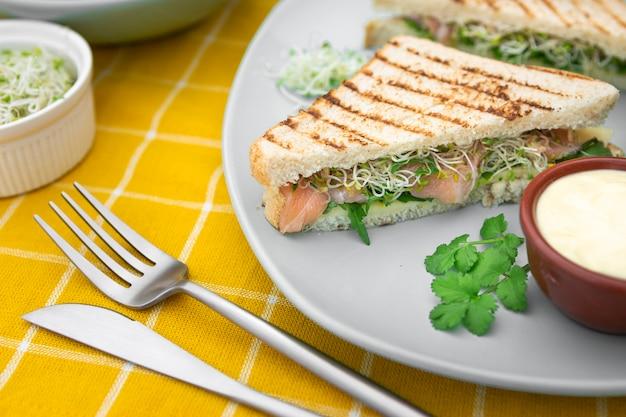 マヨネーズとカトラリーのプレート上の三角形のサンドイッチ