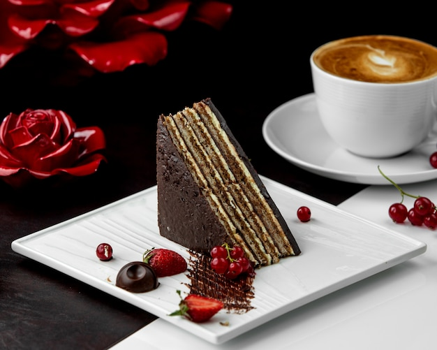 Triangular-shaped cacao layered cake served with berries