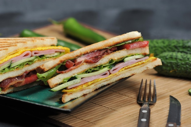 Triangular shaped sandwiches with ham and omelet on a plate