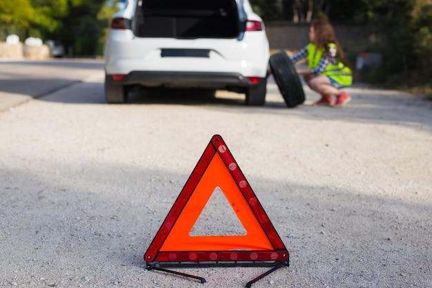 車輪を変えようとしている女の子の壁の事故の三角形の兆候