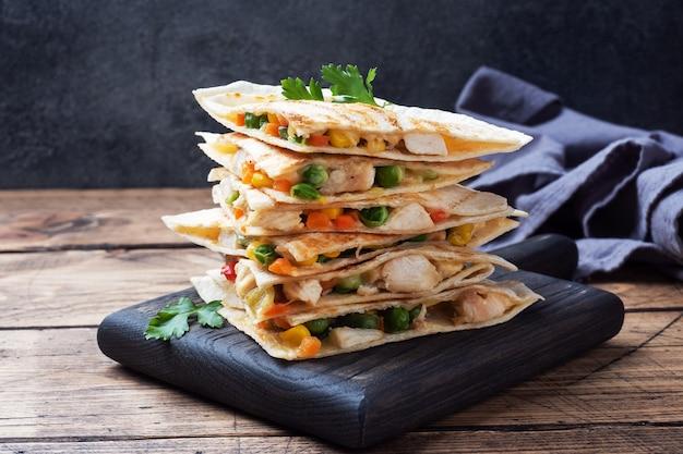Треугольные ломтики мексиканской кесадильи с соусом.