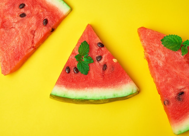 Triangular slices of ripe red watermelon with seeds background