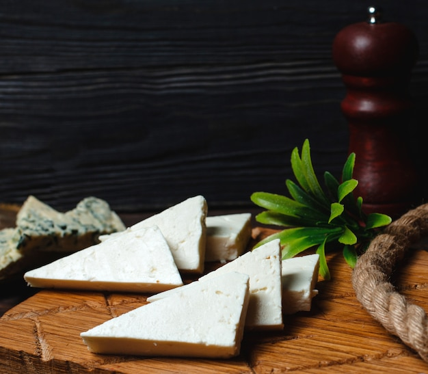 Triangulated white cheese on a wooden board