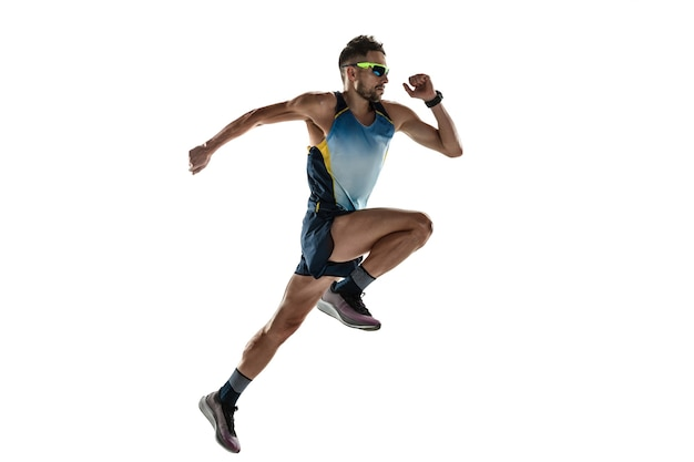 트라이애슬론 남자 선수는 흰색 스튜디오 배경에 격리되어 실행됩니다. 백인 맞는 조깅 선수, 스포츠 장비를 착용한 철인 3종 경기 선수. 건강한 라이프 스타일, 스포츠, 액션, 모션의 개념. 점프에서.