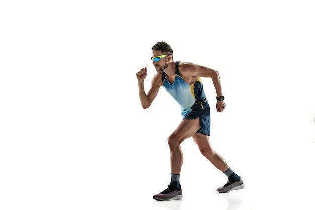 트라이애슬론 남자 선수는 흰색 스튜디오 배경에 격리되어 실행됩니다. 백인 맞는 조깅 선수, 스포츠 장비를 착용한 철인 3종 경기 선수. 건강한 라이프 스타일, 스포츠, 액션, 모션의 개념. 측면보기.
