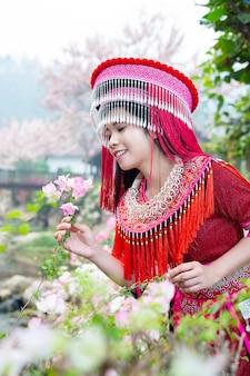 公園の赤い伝統的な衣装で部族の美しい女性