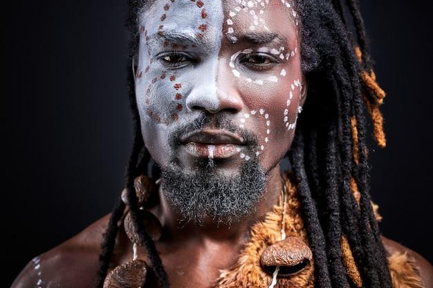 エスニックな本物のメイクをした部族の男が正面を見る