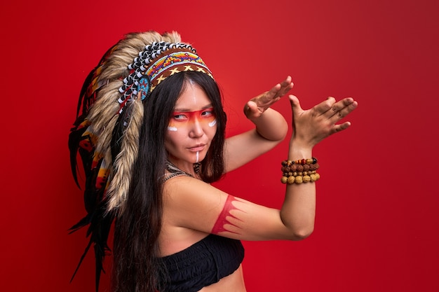 Tribal indian woman dancing during ritual wearing shaman costume isolated over red wall
