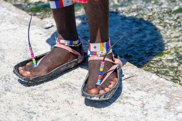 カラフルなブレスレットと車のタイヤで作られたサンダルを備えた部族のマサイ族の足