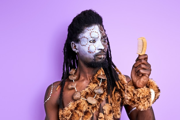 Tribal primitive male looks at comb, he doesn't know how to use it, isolated over purple wall
